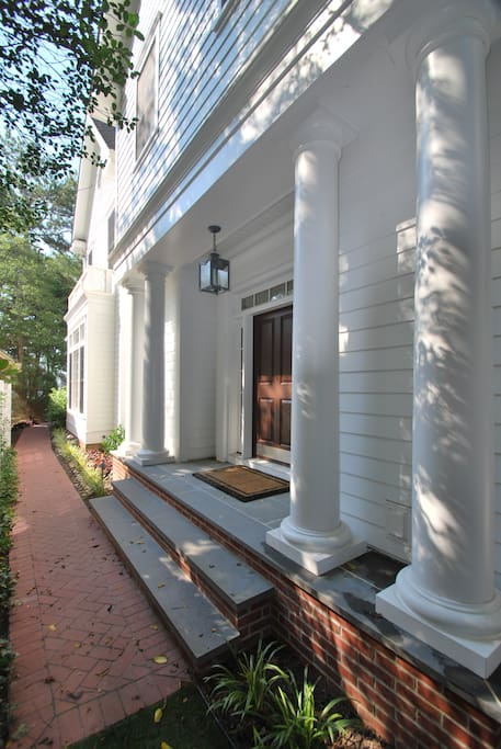 The house is entered through an impressive columned side entrance.