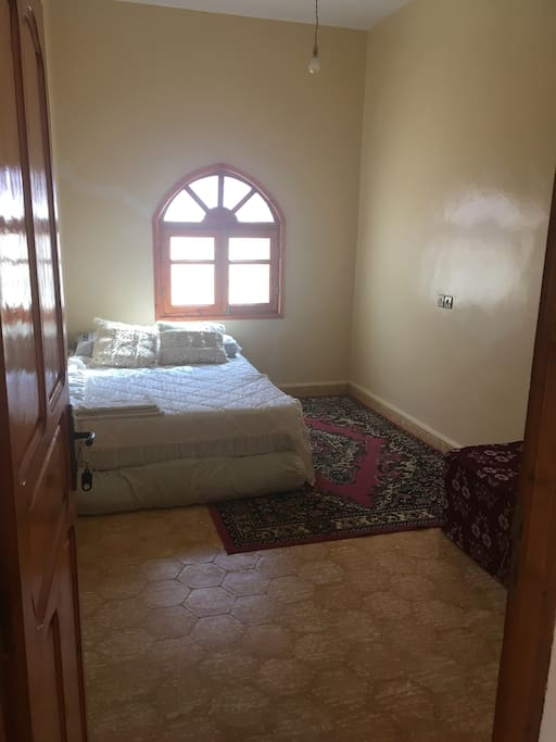 Habitación de invitados con cama de matrimonio perchero dos puuf, un perchero,puerta con llave, ventana con rejas y mosquiteros