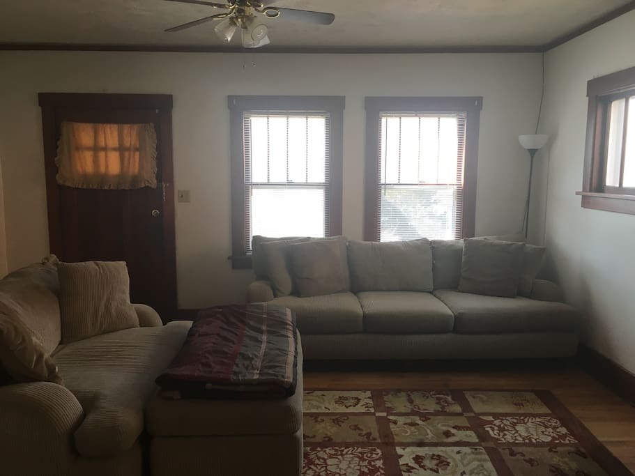 Living room area with couch & love seat with view to front porch.