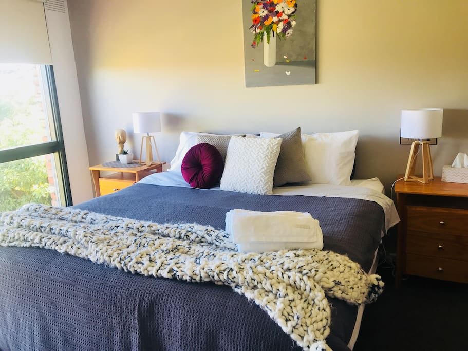 The Master Bedroom has an antique dresser, a comfy tub chair, a beautiful view, an ensuite with double showers and a huge walk-in dressing room.