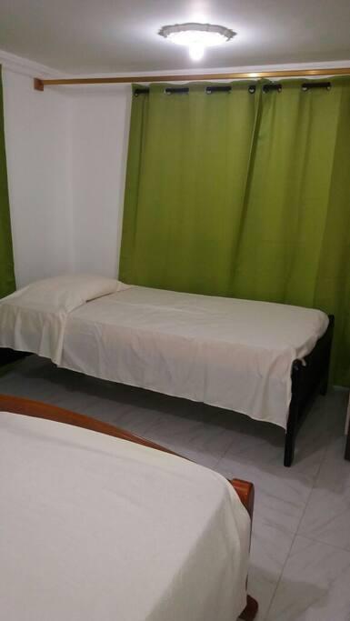 Una habitación con 2 camas una sencilla y una doble