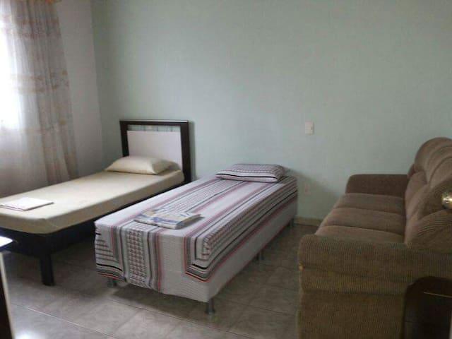 Quarto com cama de solteiro, para duas ou três pessoas.