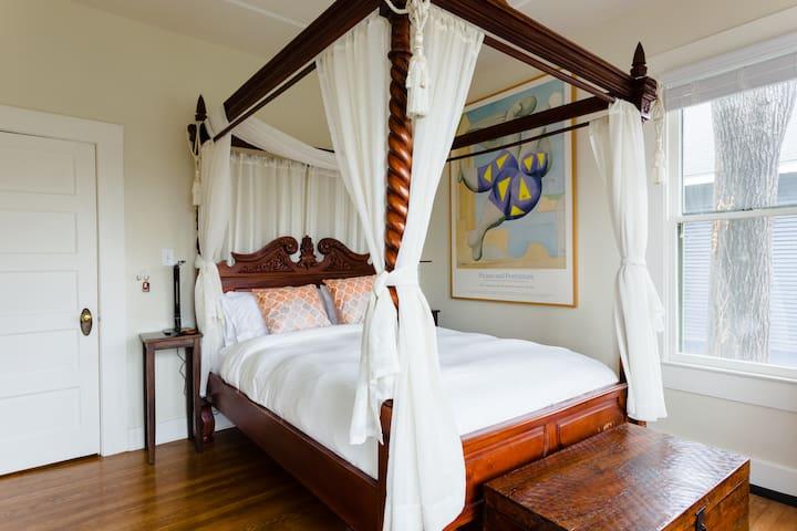 Master bedroom: hand-carved mahogany canopy bed.