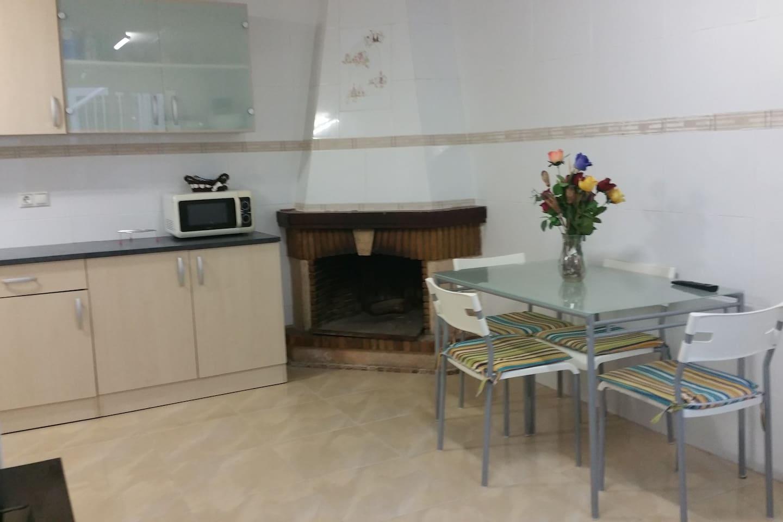 cuisine du rez de chaussée de la maison 25 mètres carrés , table pour 4 personnes ,cheminée,cuisine aménagée micro onde ,grille pain , télévision écran plat