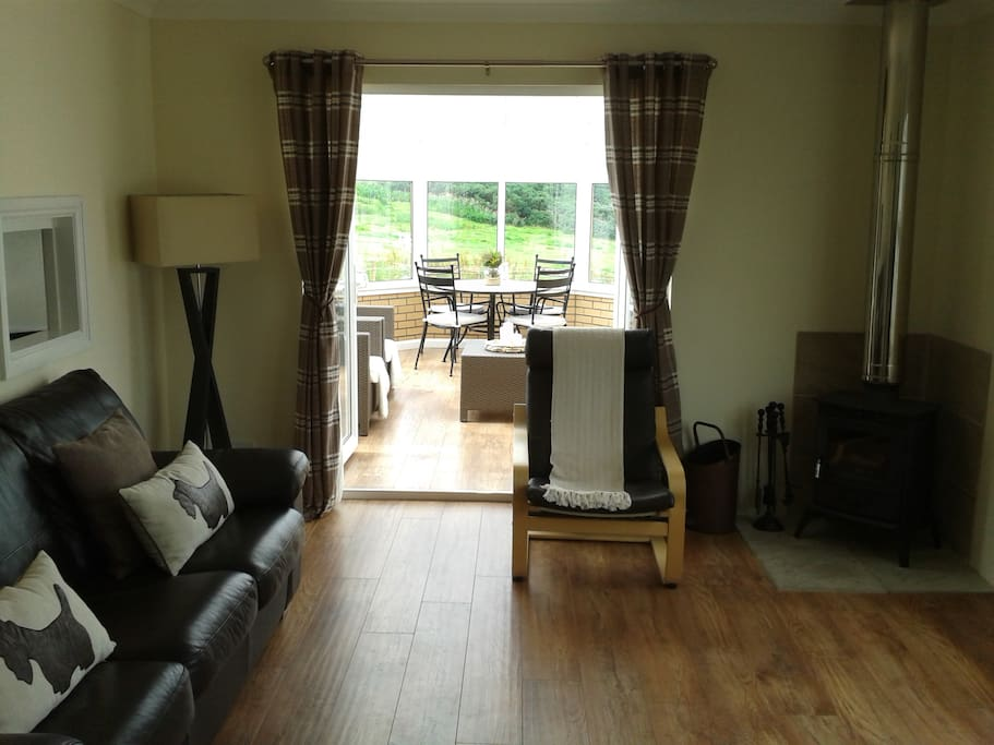 Spacious living room with sea view, log burning stove and luxury sofa bed.