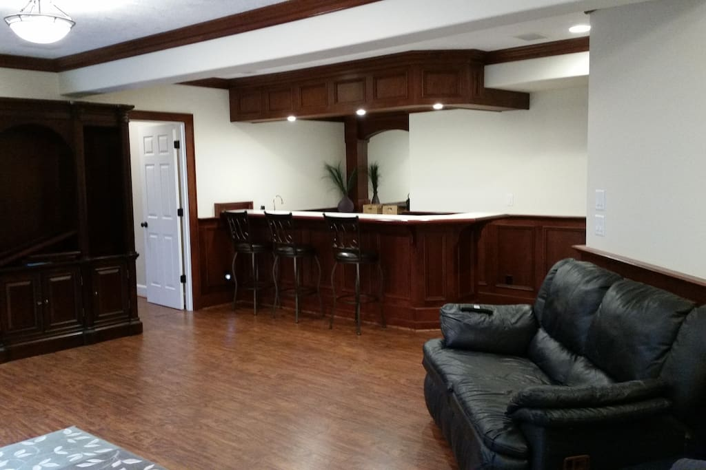 Large private living room with sofa bed, leather sofa and TV.  Breakfast bar, refrigerator, microwave and sink.