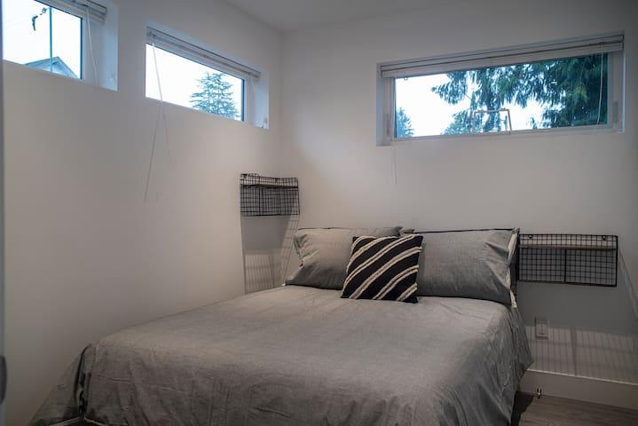 Main floor bedroom with double bed, dresser & closet.
