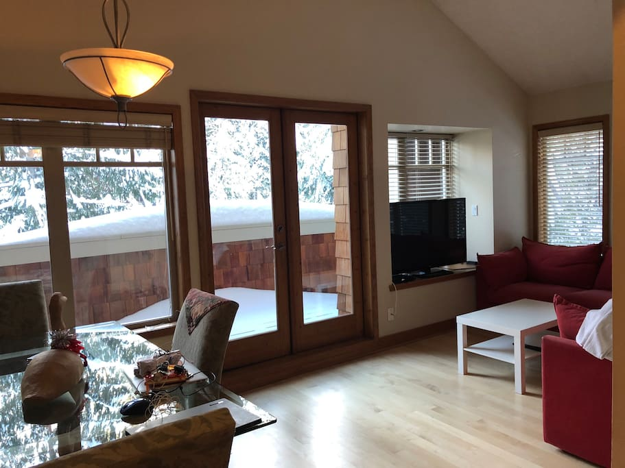 Your living room in the winter, with fresh powder snow on the deck, double French doors, glass dining table.