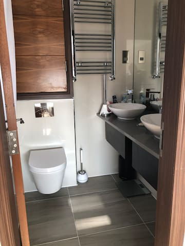 Private guest bathroom with double sinks and bath/shower