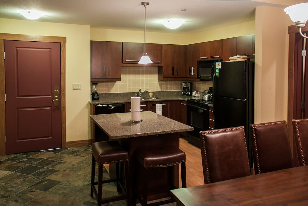 Fully stocked kitchen with island and upgraded countertops.