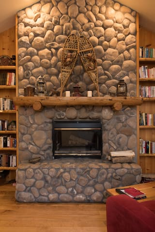 See-through rock wall fireplace and library.