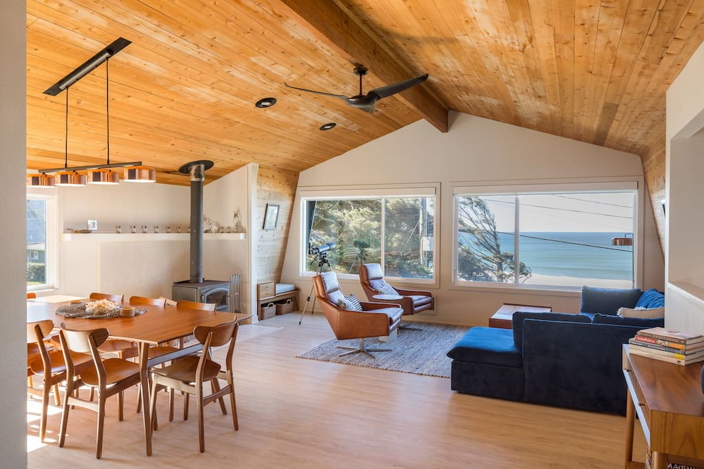The open-plan 3rd floor living space serves as a social heart of the home. Kick back with a book on a comfy blue sectional, enjoy the ocean views, or cozy up in front of a wood-burning stove.