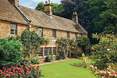 Historic manor house surrounded by mature gardens