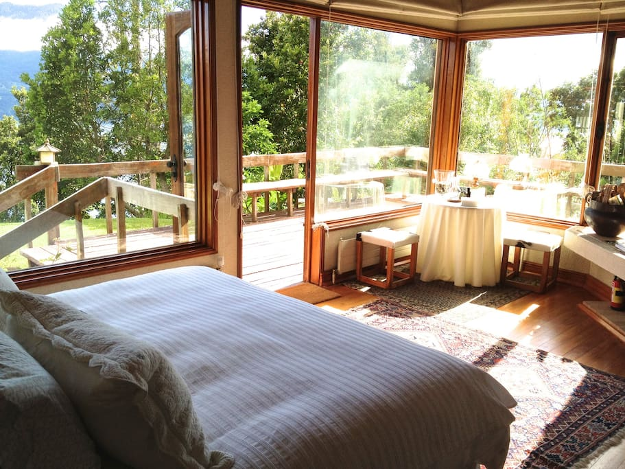 Master bedroom features a king-sized bed and spectacular wrap-around lake views.