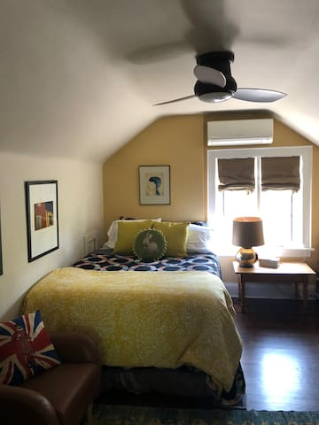 Cheerful bedroom with queen bed, flat screen tv, ceiling fan and air conditioning