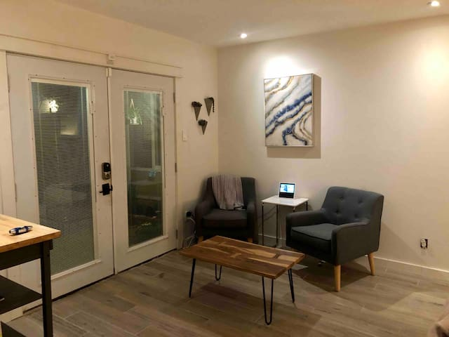 """Seating area for 2 to relax and watch 49"""" smart TV or enjoy coffee looking out onto the garden patio."""