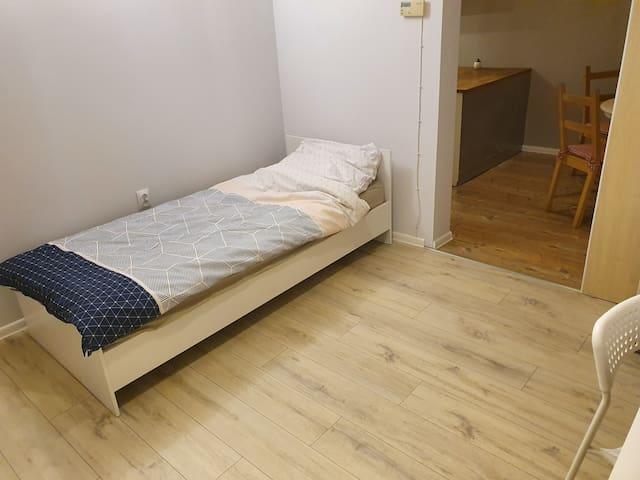 Room with 2 beds, sliding door to kitchen