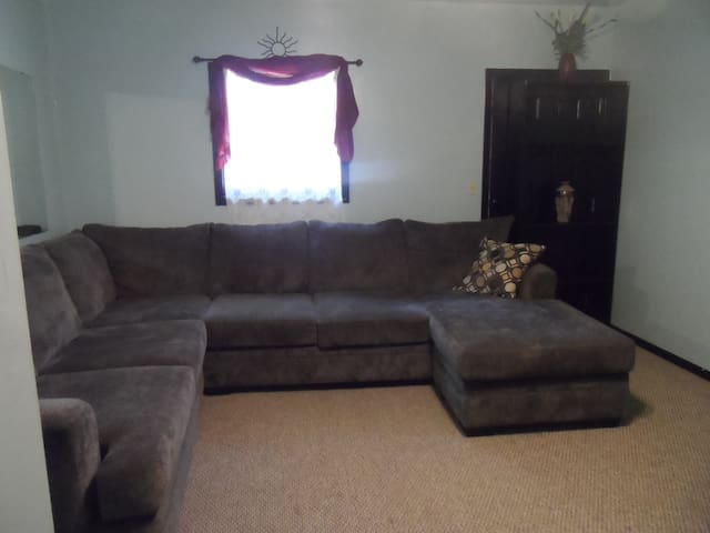 Living room with comfy wrap couch to watch flat screen  tv, visit or play games.