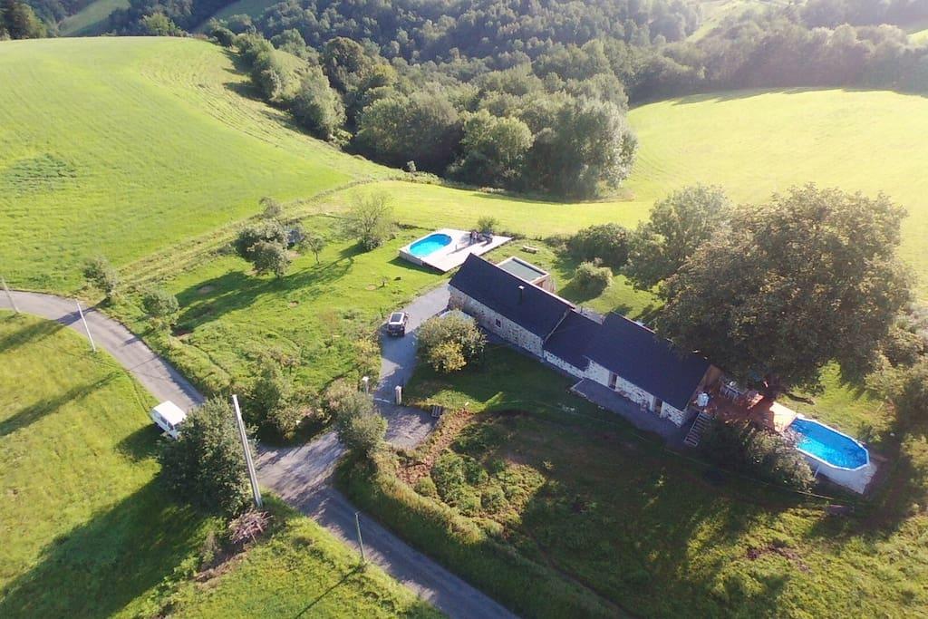 Le gîte se trouve sur la droite avec la piscine puis la terrasse bois et le jacuzzi se trouve à l'abri des regards en dessous...