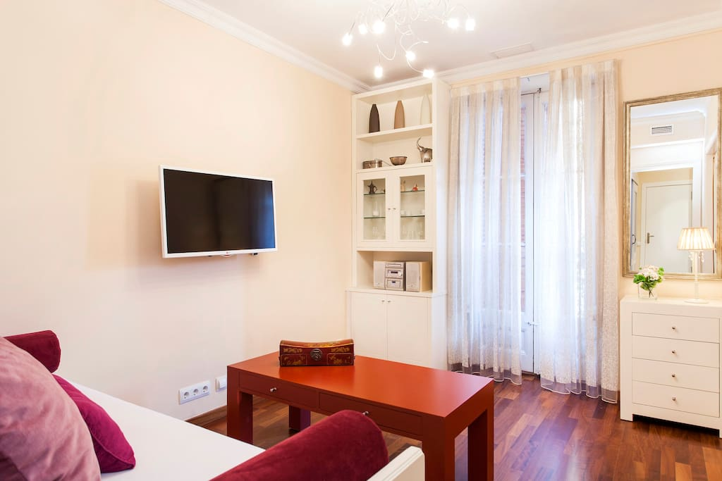 Sitting area with wide screen satellite TV, spacious sofa and coffee table