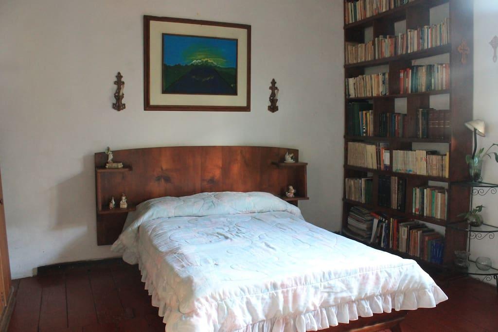 Alcoba con cama en madera antigua y amplios espacios