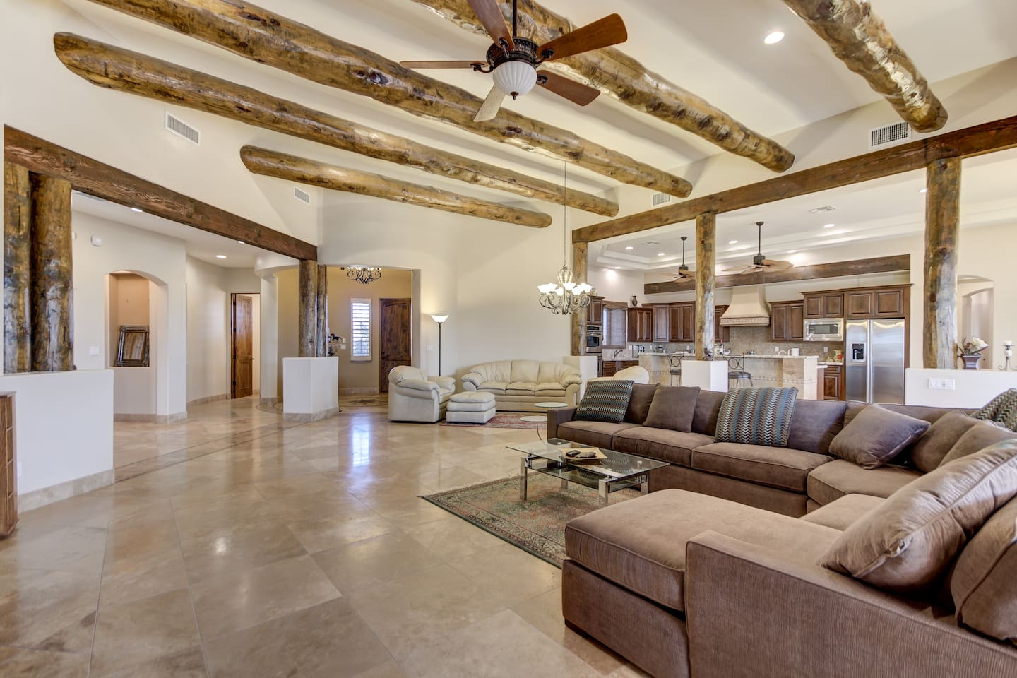Living area with couches, TV and indoor fireplace and open concept kitchen.