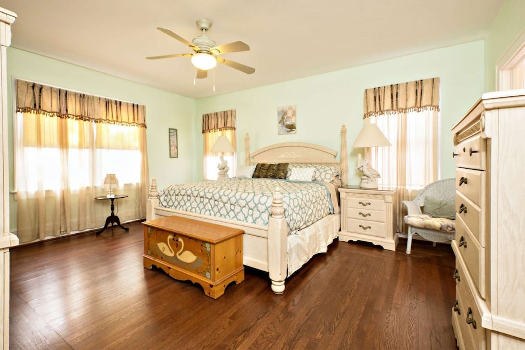 Master bedroom features king size bed, ceiling fan and adjoining private bathroom.