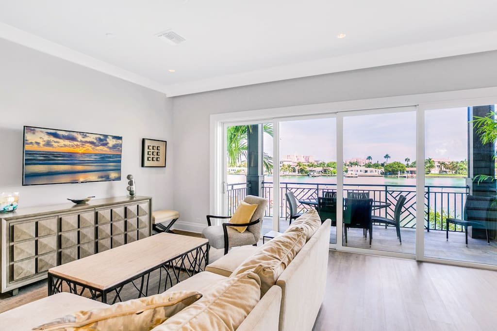 Living room with a comfortable sectional couch, workstation and a balcony with a beautiful view