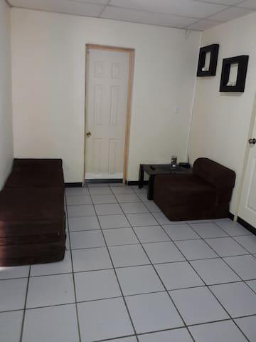 Sala de estar. Equipado con 3 sofa cama color cafe  ( hay 2 extendidos de muestra)¿ wifi. En medio la puerta del baño