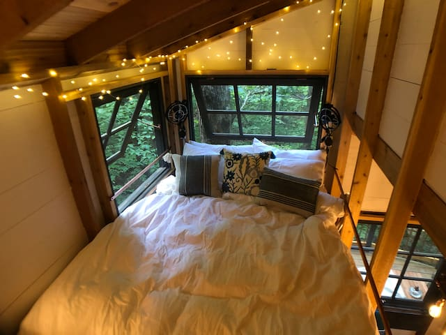 A cozy queen bed in the loft overlooks the forest and a small stream.