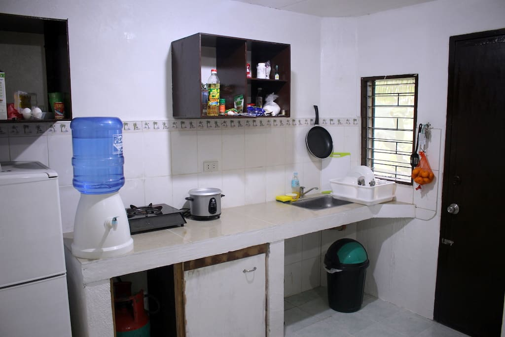 The kitchen - fridge, gas stove, rice cooker, kettle, plates and cutlery.