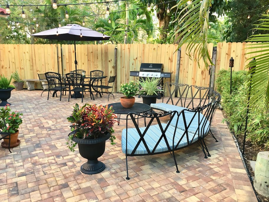 Shared paver patio with curved sofa and dining table that seats 8 with BBQ for convenience.
