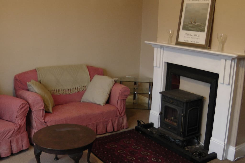 living room with bay window, log burner, tv, dining table x8, sofas for 6