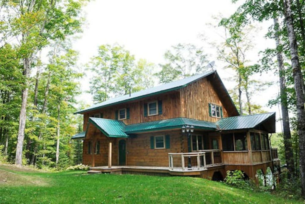 Exterior, front.  Beautiful log home amongst the trees, on the lake