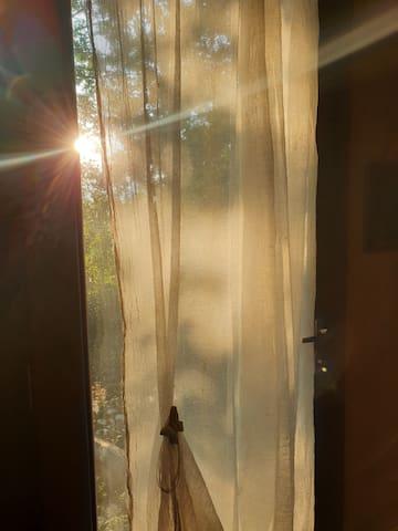 La cucina si apre sull'ombreggiato retro della casa tramite una porta a vetri, fantastica al tramonto -  The kitchen opens onto the shaded back of the house through a glass door, fantastic at sunset
