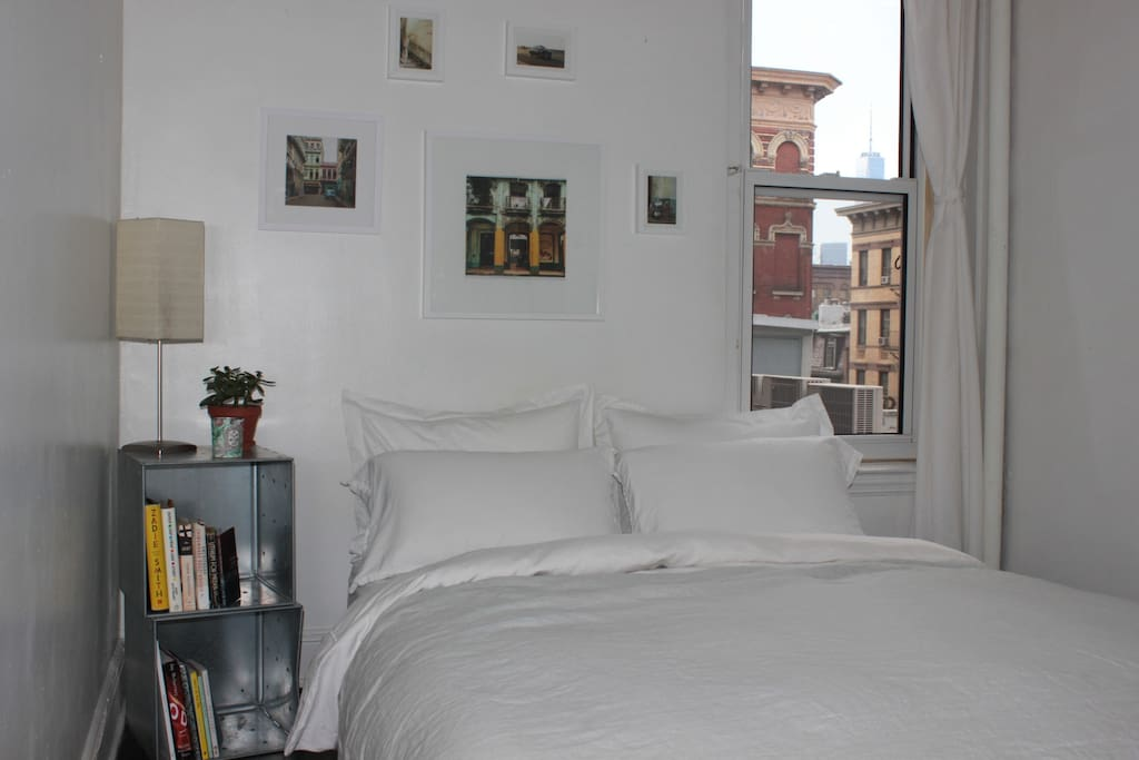 Your bedroom:  Quiet and sun-drenched. Comfy, new queen bed with plush mattress. View of the Freedom tower.