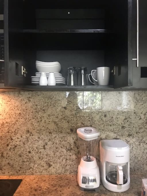 Mugs, glasses, plates, coffee maker and blender.