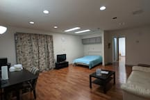 Living room with couch and TV, full size bed, desk, mini bar, microwave, and window with view of the lobby