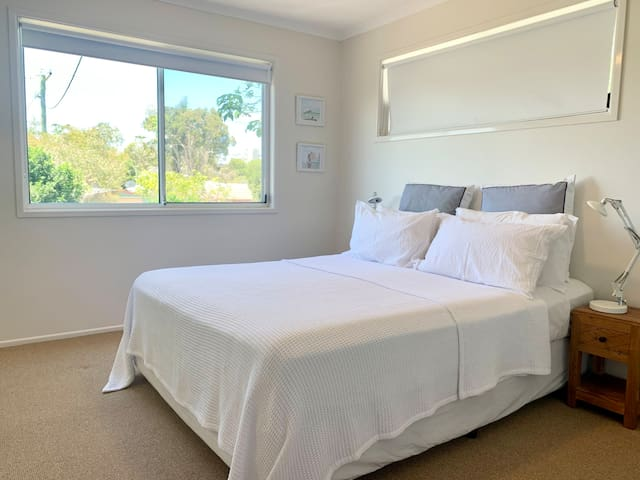 One of the bedrooms. It offers a comfortable queen size bed for your total relaxation after an eventful day. Wake up in the morning, get a lot of natural light, and feel the beautiful nature outside.