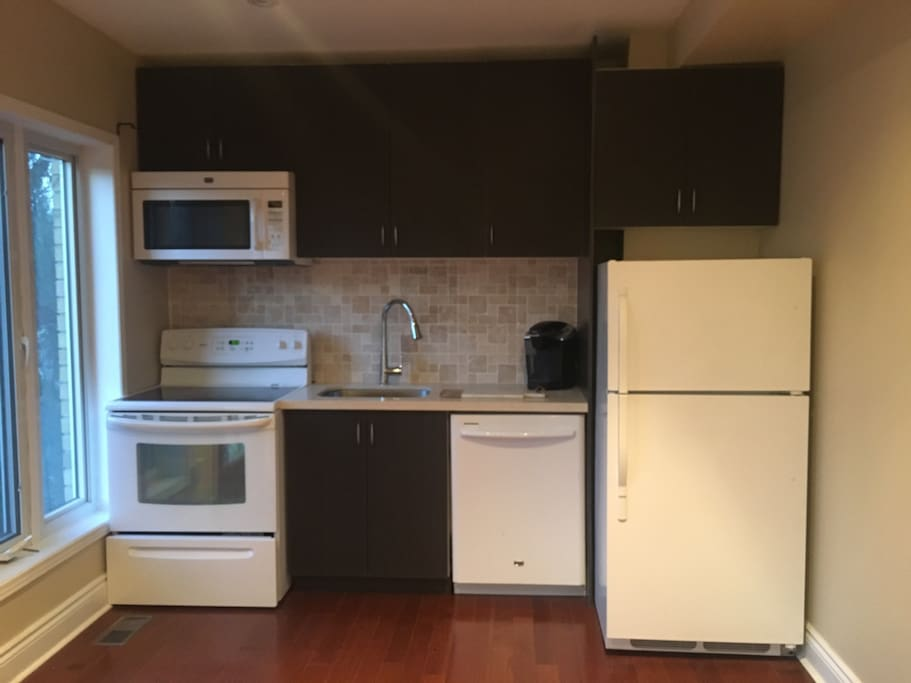 Kitchen with fridge, microwave, stove, sink, and dishwasher.