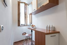 The  kitchen  counter with a stool and a window with a nice view over the neighbor's garden.