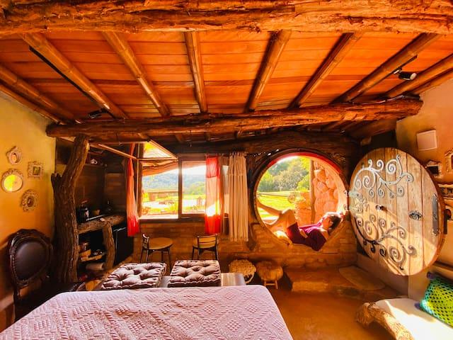 Visão ampla do quarto da Hobbit House pela manhã, quando o sol acaba de nascer