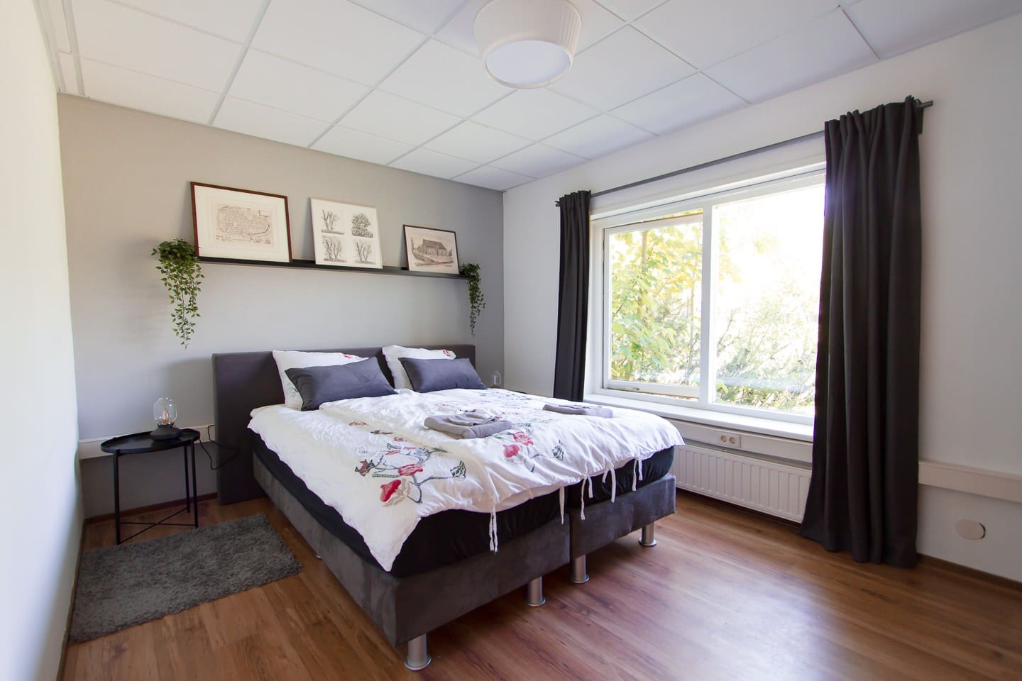 Master bedroom with a boxspring double bed. The bedroom looks out over a meadow for a splendid morning view.