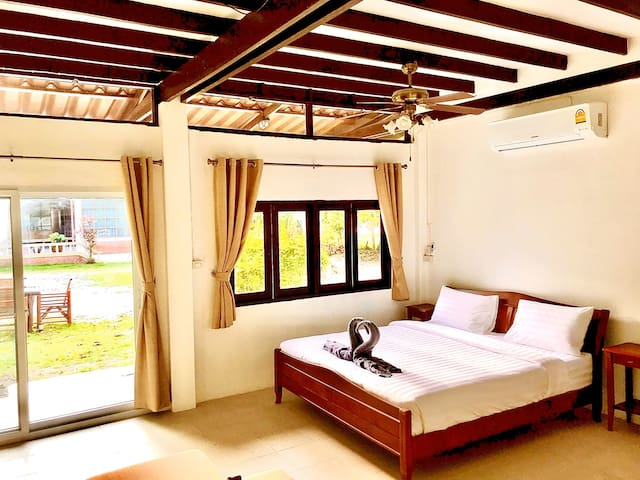 King Bed with overhead fan and air conditioning.  Patio doors to front garden and sea views