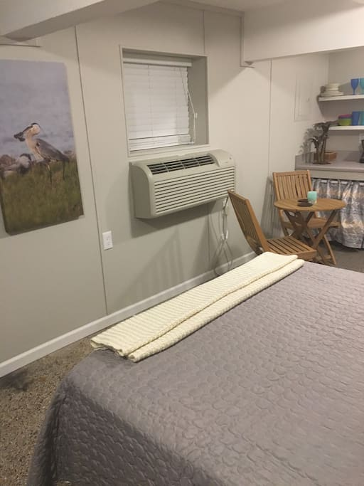 Queen bed, AC unit, and seating