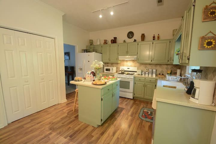 This Kitchen is bright and airy and has an island with stools for eating