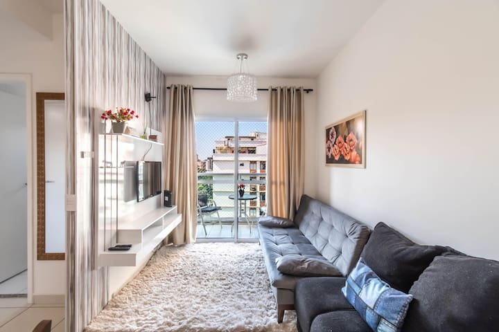 Sala de estar com TV, ventilador portátil, varanda, sofá cama pra duas pessoas e mais sofá para duas.
