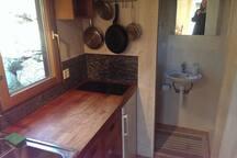 Arbeitsfläche mit Kochstelle (Induktion) und Blick ins kleine Duschbad