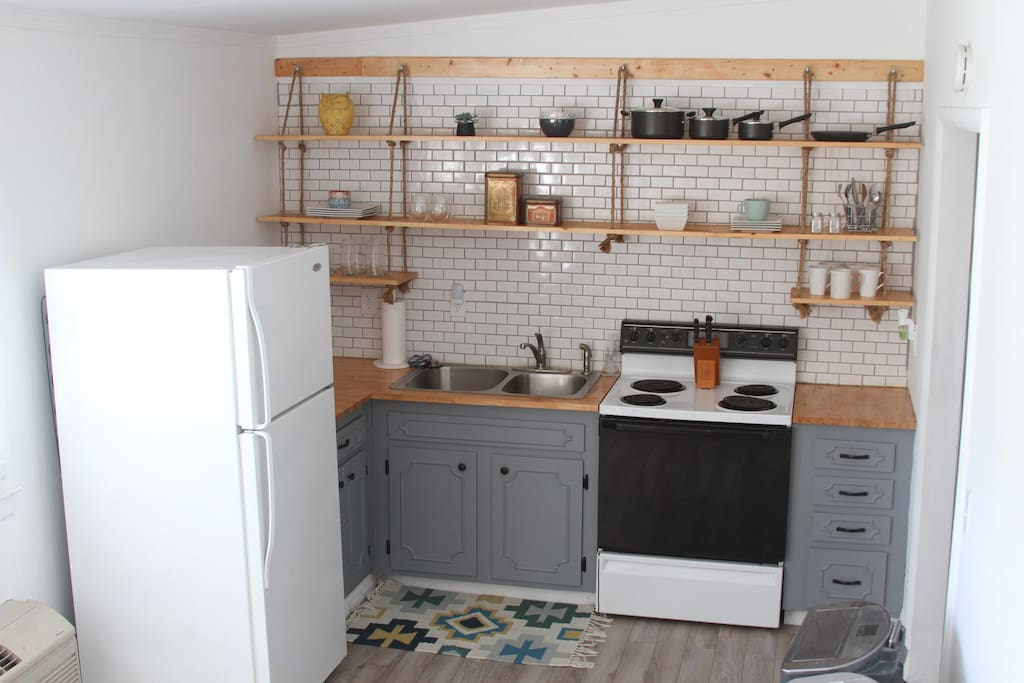Full kitchen with keurig, microwave, cooking supplies, and dining table.