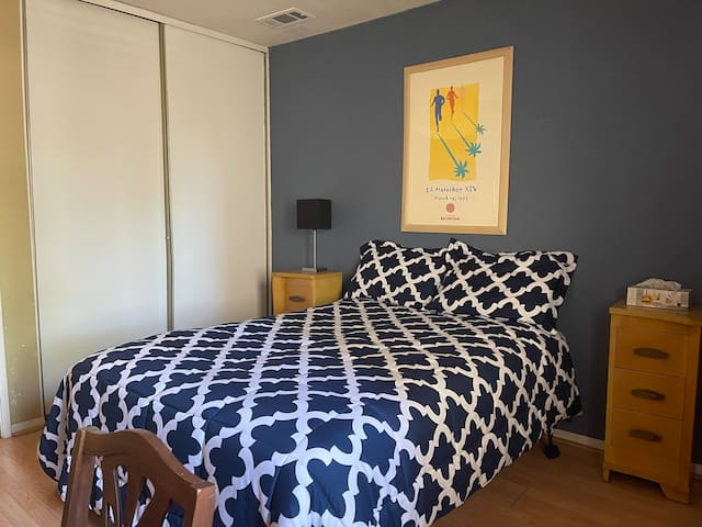 Comfy Full Sized bed with comforter and relaxing pillows. Two night stands are right next to the bed, one on each side.